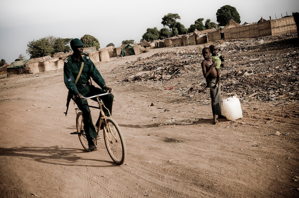 A soldier rides his bicycle in the Southern Sudanese town of Aweil. Sudan recently voted on whether or not to remain with the North or to set out alone as the world's newest nation. (© William B. Plowman)