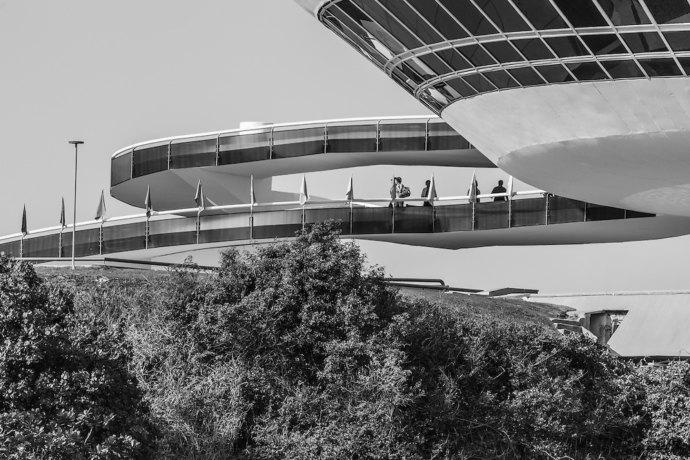 The Niter&oacute;i Contemporary Art Museum (Museu de Arte Contempor&acirc;nea de Niter&oacute;i &mdash; MAC) is situated in the city of Niter&oacute;i, Rio de Janeiro, Brazil, and is one of the city&rsquo;s main landmarks. It was completed in 1996.<br /> <br /> Designed by Oscar Niemeyer with the assistance of structural engineer Bruno Contarini, who had worked with Niemeyer on earlier projects, the MAC-Niter&oacute;i is 16 meters high; its cupola has a diameter of 50 meters with three floors. The museum projects itself over Boa Viagem (&ldquo;Bon Voyage,&rdquo; &ldquo;Good Journey&rdquo;) beach and also a neighborhood, the 817 square metres (8,790 sq ft) reflecting pool that surrounds the cylindrical base &ldquo;like a flower,&rdquo; in the words of Niemeyer.[citation needed]<br /> <br /> A wide access slope leads to a Hall of Expositions, which has a capacity for sixty people. Two doors lead to the viewing gallery, through which can be seen Guanabara Bay, Rio de Janeiro, and Sugarloaf Mountain. The saucer-shaped modernist structure, which has been likened to a UFO, is set on a cliffside, at the bottom of which is a beach. In the film Oscar Niemeyer, an architect committed to his century, Niemeyer is seen flying over Rio de Janeiro in a UFO which then lands on the site, suggesting this to be the origin of the museum.