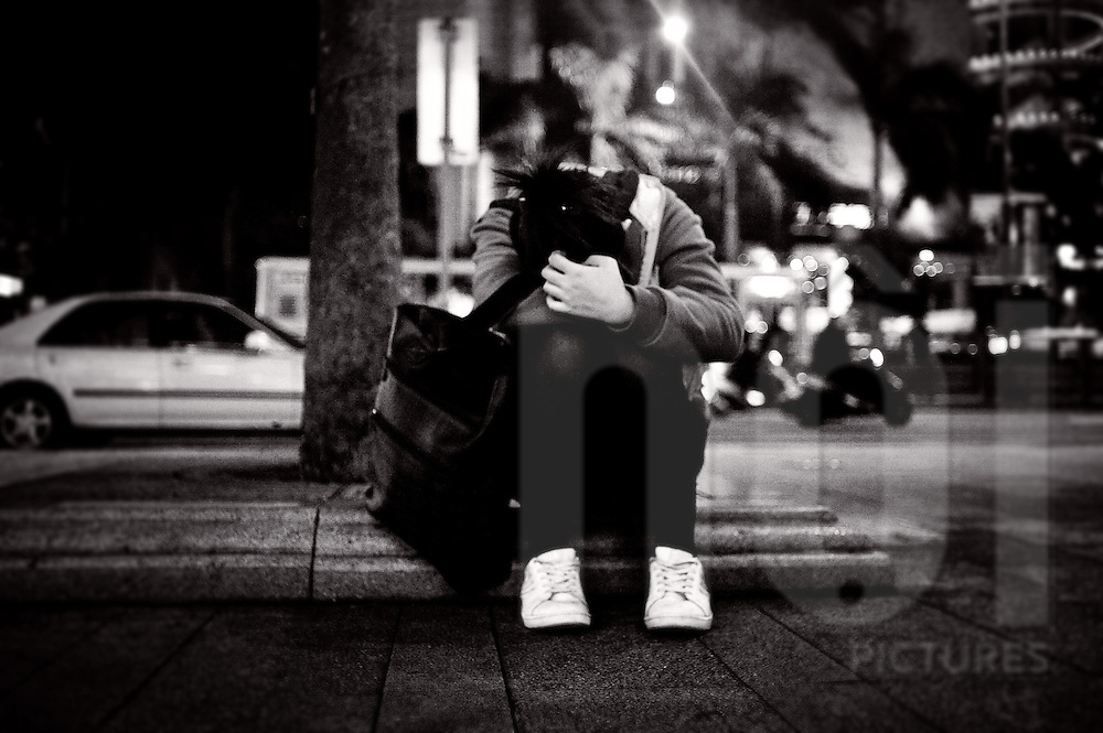 A girl sits on the sidewalk with her head on her arms, Taipei, Taiwan, Asia
