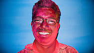 Indian man covered in red paint during Holi Festival in front of blue wall.