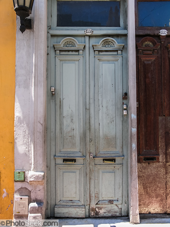 "An old wood double door is painted light blue in San Telmo barrio, the heart of old Buenos Aires, Argentina, South America. Admire well-preserved old buildings in San Telmo (""Saint Pedro González Telmo""), the oldest barrio (neighborhood) of Buenos Aires."