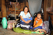 "Peng Souvanthon, age 26, Team Leader, with her 2 day old son and 6 year old daughter at home.  Even at 8 months pregnant she worked in remote Nong Het field locations clearing bombs up until the day she gave birth...""I used to be a farmer. My background is useful because even if the weather conditions are difficult I can still do my job. At that time my husband and I had no cash income so it was hard to look after our baby. So when MAG was recruiting VAC (Village Assisted Clearance) team members, I applied. At first I cut vegetation, then I was trained to use a detector. The technical field manager saw I had progressed and encouraged me to apply to become a technician. I passed the test. Then after a while I was promoted to deputy team leader and now team leader. My family are very proud, and I am happy! I enjoy managing things - the team members, the equipment and the site. And I remember everything I have learned during the training. To ge a good team leader you must show your love for your team members. You must discuss everything with them, and carefully go through the workplan with them each day. And you must help anyone who has difficulties.""...Laos was part of a ""Secret War"", waged within its borders primarily by the USA and North Vietnam.  Many left over weapons supplied by China and Russia continue to kill.  However, between 90 and 270 million fist size cluster bombs were dropped on Laos by the USA, with a failure rate up to 30%.  Millions of live cluster bombs still contaminate large areas of Laos causing death and injury.   ..The women of Mines Advisory Group (MAG) work everyday under dangerous conditions removing unexploded ordinance (UXO) from fields and villages...***All photographs of MAG's work must include (either on the photo or right next to it) the credit as follows:  Mine clearance by MAG (Reg. charity)***."