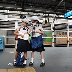 Schoolgirls waiting for the train at a railway station, Tokyo, Japan, Asia.