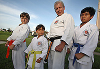 Karate coach Vicente Gonzalez, second from right, poses with his students, from left, Alejandro Casuso, 9, Dylan Aleman, 5 and John Paulo, 10 after their training session at Sunset Lake Community Center on Monday July 6, 2009. Staff photo/Cristobal Herrera..