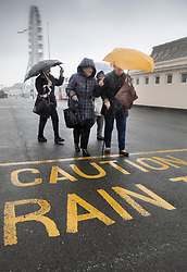 © Licensed to London News Pictures. 14/08/2019. West Sussex, UK. A group of day-trippers from Bermondsey, south London brave the wind and rain on the seafront at Worthing on the south coast. Parts of the United Kingdom are exeriencing heavy unseasonable rain today. Photo credit: Peter Macdiarmid/LNP