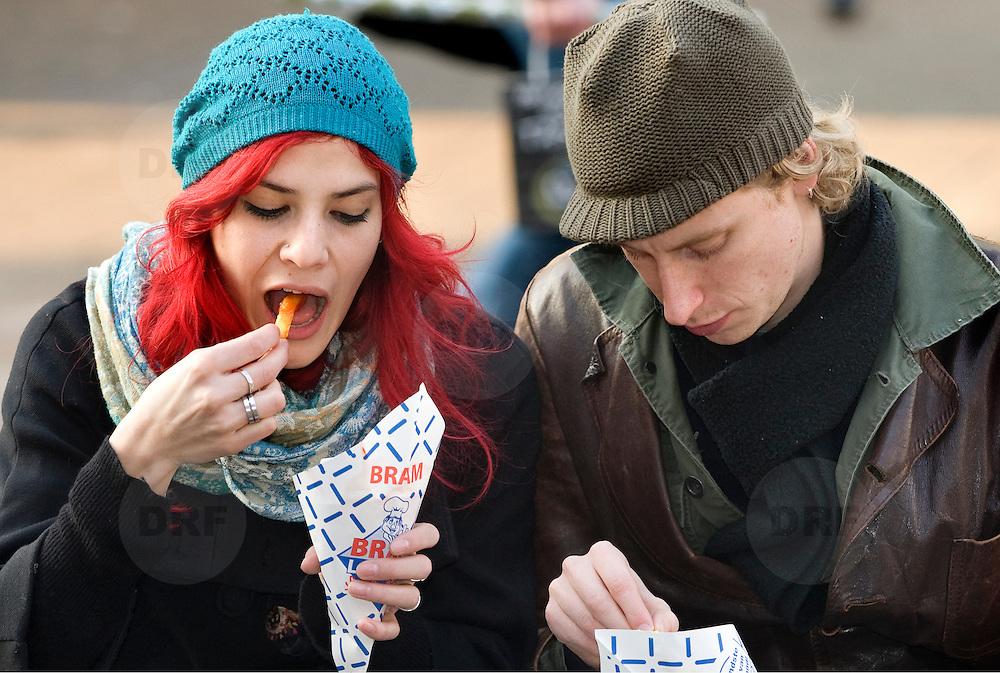 Nederland Rotterdam 18 februari 2008 20080218 .Een stel eet papat/ snackt op een bankje in de zon op Binnenwegplein in centrum Rotterdam ..'Vettax' goed middel tegen ongezond eten.Extra accijns op ongezonde levensmiddelen als drank, tabak en snacks, is een goede methode om consumenten gezonder te laten eten. Dat is een van de ideeën van de Raad voor de Volksgezondheid en Zorg (RVZ) om mensen meer verantwoordelijk te maken voor hun eigen gezondheid...Foto David Rozing/