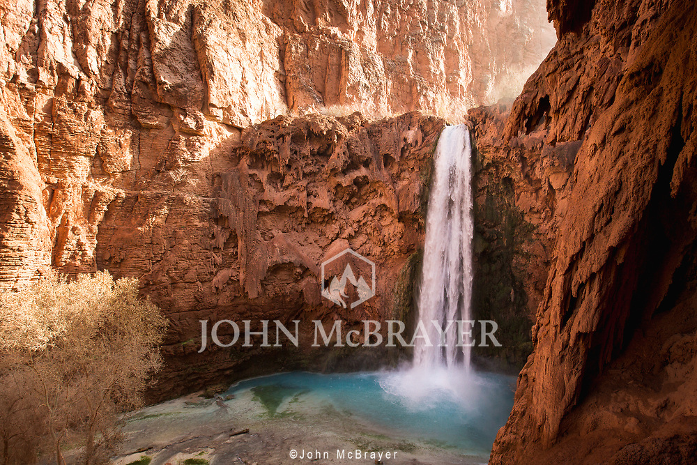 The blue green waters of Havasu Creek contrast the red rocks as they cascade down the 200 foot waterfall. These falls are a 12 mile hike into the Havasupai Reservation located on the south rim of the Grand Canyon.  © John McBrayer