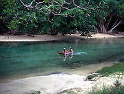 Two tourist children paddle on lilo at Frenchman s Creek, Jamaica