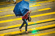 13 AUGUST 2013 - HONG KONG: People cross Des Voeux Road in Hong Kong during rains from Typhoon Utor. Typhoon Utor (known in the Philippines as Typhoon Labuyo) is an active tropical cyclone located over the South China Sea. The eleventh named storm and second typhoon of the 2013 typhoon season, Utor formed from a tropical depression on August 8. The depression was upgraded to Tropical Storm Utor the following day, and to typhoon intensity just a few hours afterwards. The Philippines, which bore the brunt of the storm, reported 1 dead in a mudslide and 23 fishermen missing at sea. The storm brushed by Hong Kong bringing several millimeters of rain and moderate winds to the island but causing no reported damage or injuries. It is expected to make landfall in China.    PHOTO BY JACK KURTZ