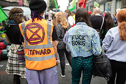 © Licensed to London News Pictures. 30/08/2019. Manchester, UK. A woman wearing a jacket with FUCK BORIS in reference to British Prime Minister Boris Johnson . Extinction Rebellion block roads, in Manchester City Centre , at the start of several days of planned disruption organised by environmental campaigners . Manchester City Council has declared a climate emergency but activists say the council's development plans do not reflect this . Photo credit: Joel Goodman/LNP