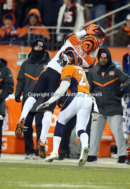 Cincinnati Bengals wide receiver Marvin Jones (82) leaps and stretches as he catches a third quarter pass while covered by Denver Broncos cornerback Chris Harris Jr. (25) during the 2015 NFL week 16 regular season football game against the Denver Broncos on Monday, Dec. 28, 2015 in Denver. The Broncos won the game in overtime 20-17. (©Paul Anthony Spinelli)