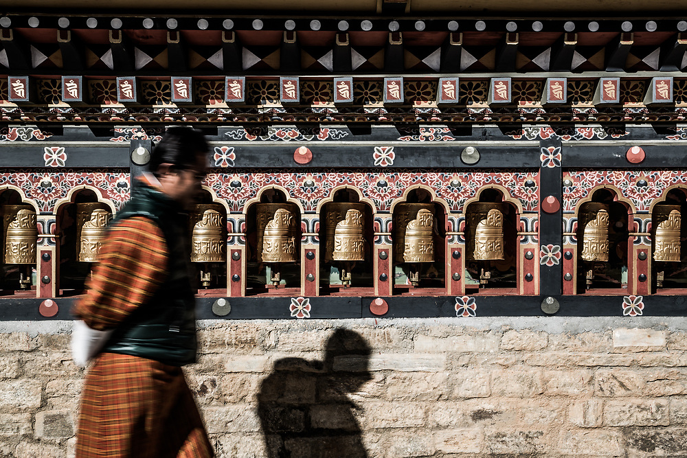 Local walking past prayer wheels in Bhutan