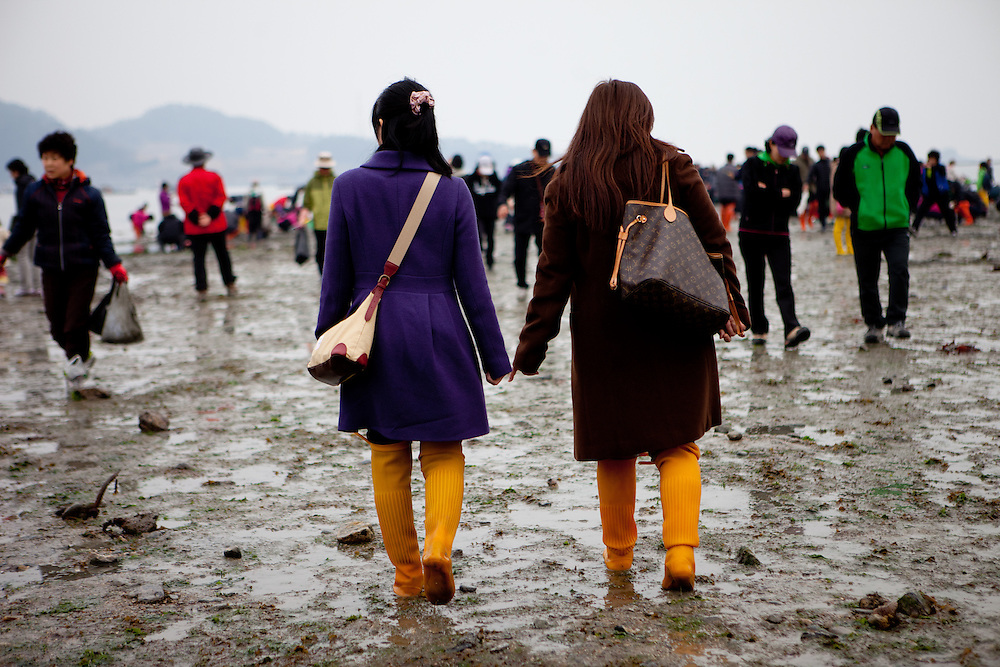 "Well dressed visitors walking the open ""Mysterious Sea Road"" at Hoedong shore (Jindo island). Jindo is the 3rd biggest island in South Korea located in the South-West end of the country and famous for the ""Mysterious Sea Route"" or ""Moses Miracle"". Every spring thousands flock to the shores of Jindo to walk the mysterious route that stretches roughly three kilometers from Hoedong to the distant island of Modo. Materializing from the rise and fall of the tides, the divide can reach as wide as forty meters."