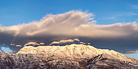 Mt. Timpanogos in Utah County lit up by the setting sun after a Winter snowstorm covered its peaks in white.
