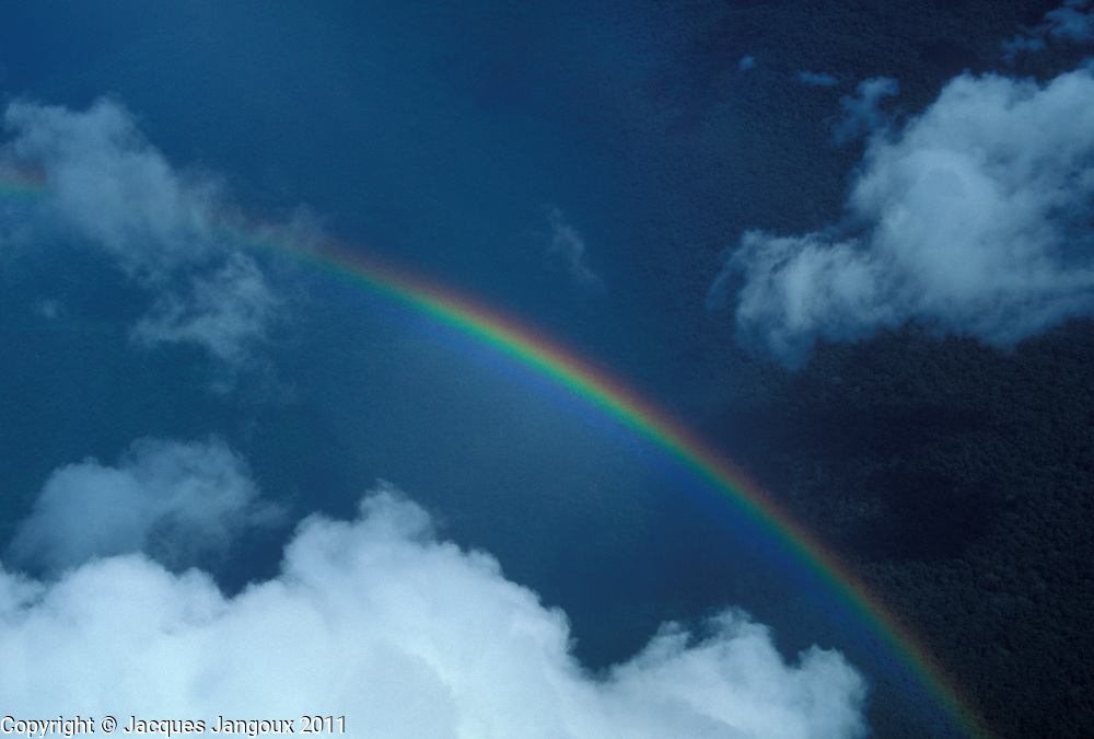 Venezuela, aerial of rainbow over rainforest in Guyana Highlands, with cumulus clouds.