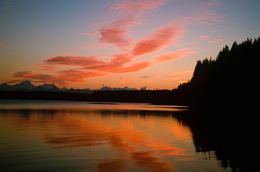 Alaska. Glacier Bay NP. Sunset light spilling onto the Beardslee Islands. The calm ocean waters of the Inside Passage in Southeast Alaska.