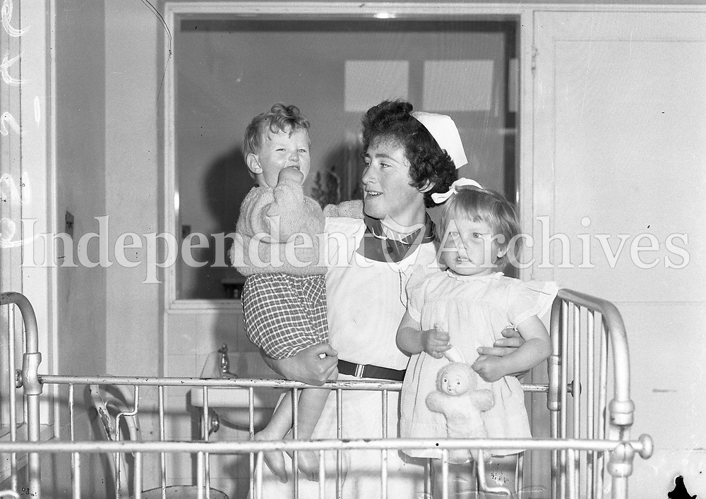 Student nurse Kathleen Naughton with two of her charges at the Children's Sunshine Home, Stillorgan annual open day. May 19 1962. <br /> <br /> History of the home:<br /> Established in 1925 as short term convalescence home.<br /> 1950's and 1960's- Admitted many very sick babies for treatment &amp;and convalescence.<br /> 1970's- Long term care of profoundly disabled children.<br /> 2002 to 2004- Strategic review to address needs of children requiring palliative care.<br /> 2006 -Expansion of the Children's Sunshine Home to incorporate LauraLynn House.<br /> 2011- Opened LauraLynn House, Ireland's first children's hospice.<br /> <br /> (Part of the Independent Ireland Newspapers/NLI Collection)