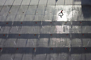 "Seen from an aerial view far above the ground level, is a young boy who leaps across a fountain water feature landscape outside Heathrow Airport's Terminal 5 building .created by the Richard Rogers Partnership (now Rogers Stirk Harbour and Partners). The highlight of a high sun glints off the wet pavement as 55 Choreoswitch waterswitches made by Ocmis are linked to 11 pumps located in a purpose built basement plant room beneath the Plaza. The switches are linked to a unit that also controls the 110 colour changing LED lights integrated into the nozzle housings. Displays can be fast and energetic with dramatic colours or subdued and gentle. From writer Alain de Botton's book project ""A Week at the Airport: A Heathrow Diary"" (2009). ."