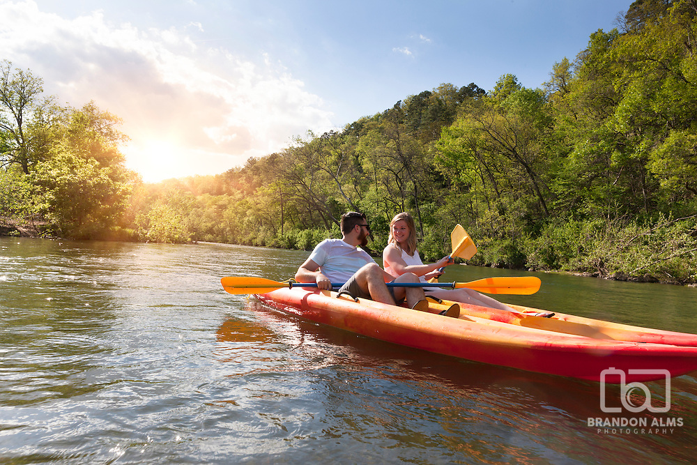 Couple having fun kayaking on a river in Missouri in the summer.