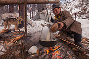 Tsaatan elder brews tea over wood fire outside teepee in taiga forest, Hunkher mountains, Northern Mongolia