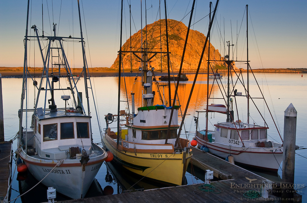 Sunrise light on Morro Rock and commercial fishing boats docked in harbor, Morro Bay, California