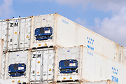A stack of white shipping containers on blue sky background