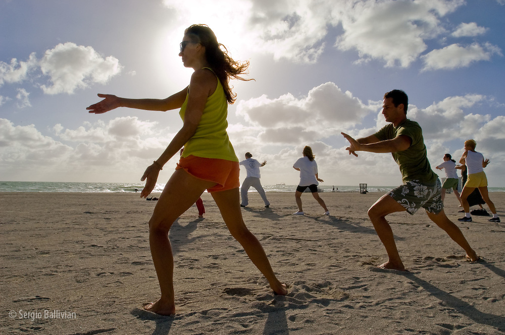 A group practices Tai-Chi on the beach in Miami Beach, Florida