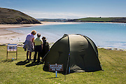 """Two British visitors admire an artists drawing overlooking Daymer Bay beach, near Trebetherick, North Cornwall, UK.  The artists has set up a camping tent and has a wooden sign on display: """"Artists at work, conversations are free""""."""