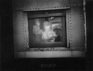 Woman holds her child in a train window, Yangon Central Railway Station, Burma