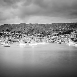 Catalina Island Avalon Bay black and white photo with boats, mountains, and hillside buildings. Santa Catalina Island is a popular travel and vacation destination off the coast of Southern California in the United States.