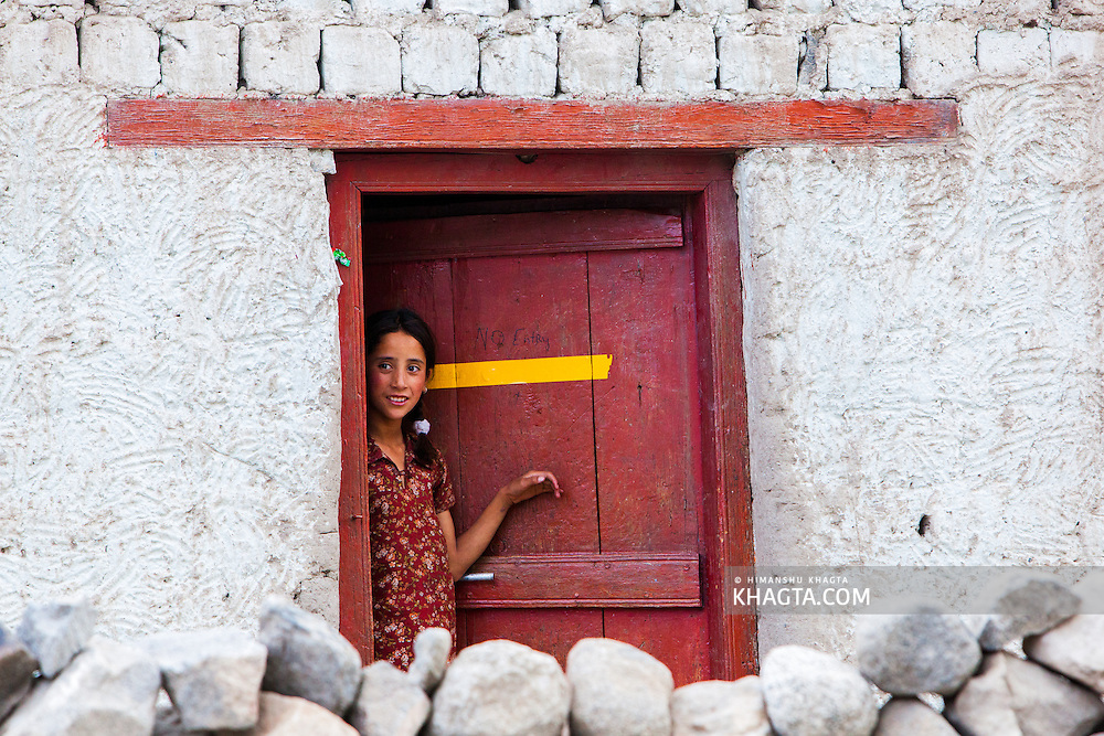A girl standing at the door of her home in Thiksey village of Ladakh