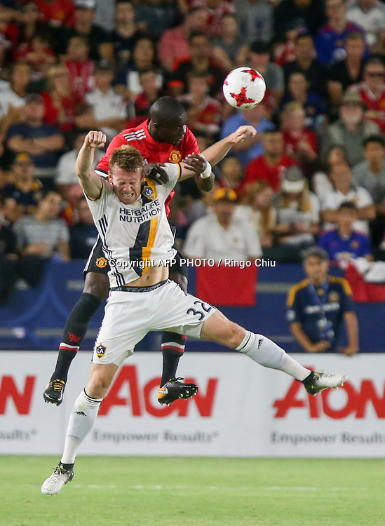 Manchester United Eric Bailly, top, and Los Angeles Galaxy Jack McBean battle for a head ball during the second half of a national friendly soccer game at StubHub Center on July 15, 2017 in Carson, California. The Manchester United won 5-2. AFP PHOTO / Ringo Chiu