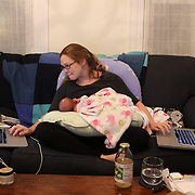 A mother breast feeds her new born baby girl while working on computers at home. Photo Tim Clayton