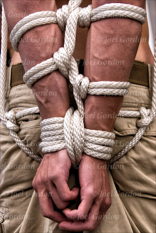 S&M Rope Bondage, close up of slave being tied up with ropes at Folsom Street East, S&M-leather-fetish themed street festival.