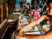 "29 DECEMBER 2018 - BANGKOK, THAILAND: A family makes longevity noodles in their shophouse. The family has been making traditional ""mee sua"" noodles, also called ""longevity noodles"" for three generations in their home in central Bangkok. They use a recipe brought to Thailand from China. Longevity noodles are thought to contribute to a long and healthy life and  are served on special occasions, especially Chinese New Year, which is February 4, 2019. These noodles were being made for Chinese New Year.        PHOTO BY JACK KURTZ"
