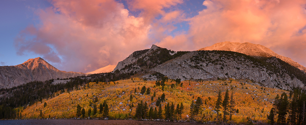 High resolution panoramic photograph of Fall color in the High Sierra up the Hilton Creek Drainage at Davis Lake. The fields of aspen are turning gold and red and a first day of fall storm moved through creating a beautiful moody sunrise. Image stitched together from 8 frames, suitable for extremely large prints or display.