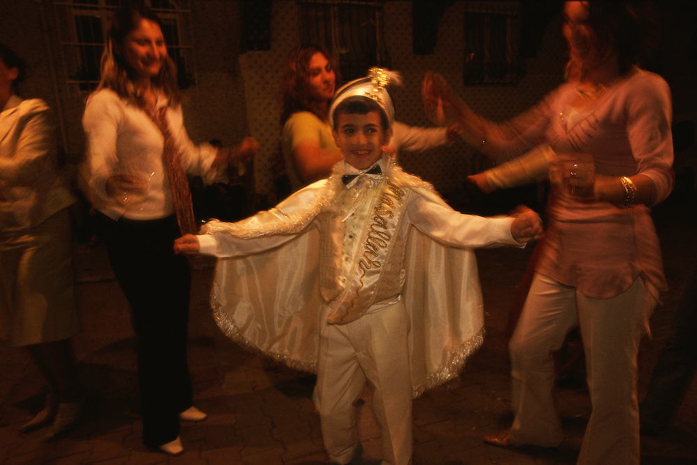 A newly circumcised boy dances with relatives and neighbors at a henna party held in the courtyard outside the family home in Istanbul, Turkey, on June 24, 2006. As is the custom, the boy is dressed in a sultan's outfit.