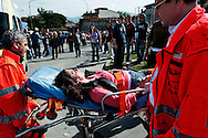 ITALY, Terzigno : A wounded woman is escorted by paramedics after clashes between police and demonstrators in Terzigno on October 18, 2010. Demontrators protest against the opening of a new dump on the slopes of Mount Vesuvius. AFP PHOTO / ROBERTO SALOMONE