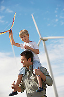 Boy (7-9) holding kite, sitting on fathers shoulders at wind farm
