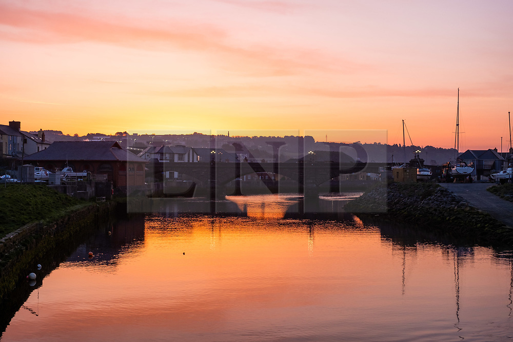 ©Licensed to London News Pictures. 19/04/2019. Aberystwyth, UK. Good Friday. Dawn breaks over the harbour and marina in Aberystwyth on the west wales coast at the start of what promises to be a glorious Good Friday, as the country looks forward to the long Easter Bank Holiday weekend. Temperatures in Aberystwyth are expected to peak in the low 70's Fahrenheit today, making it hotter than many places in continental  Europe.<br />