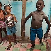 From left to right, neighbors Mariana Dilu Hernandez, 9, Stefanie Pelegrino, 7, and Davey Adria, 10, clown around in the passageway of their apartment building in the Havana, Cuba neighborhood of Jesus Maria.  The wood supports under which they are playing are holding up the deteriorating roof above the passageway.  Photo by Jen Klewitz