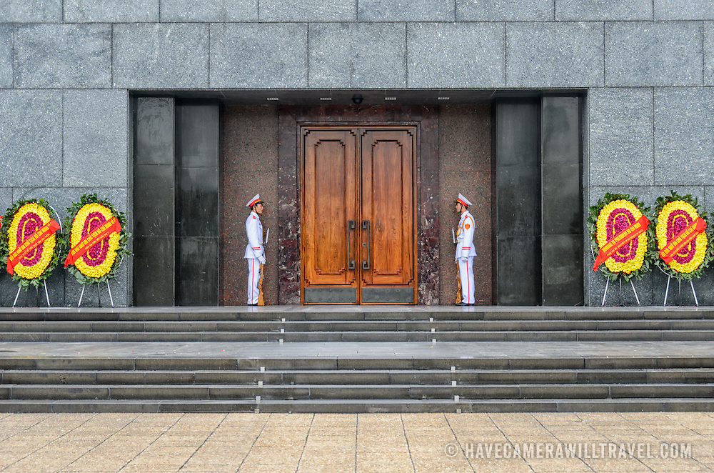 Two guards in full dress uniform stand guard at the entrance to the Ho Chin Minh Mausoleum. A large memorial in downtown Hanoi surrounded by Ba Dinh Square, the Ho Chi Minh Mausoleum houses the embalmed body of former Vietnamese leader and founding president Ho Chi Minh.