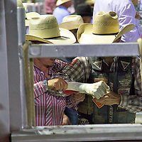 A young bull rider making last minute adjustments to his bull riding glove.