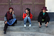 Tibetan women chat on the street in Dukezong (Old town) Shangri-la, Yunnan, China; September, 2013.