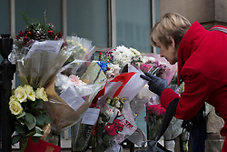 © licensed to London News Pictures. London, UK 13/12/2012. People looking at the flowers which left outside King Edward VII hospital's staff building for Jacintha Saldanha, the nurse who apparently took her own life after being duped by two Australian DJ hoax callers. Photo credit: Tolga Akmen/LNP