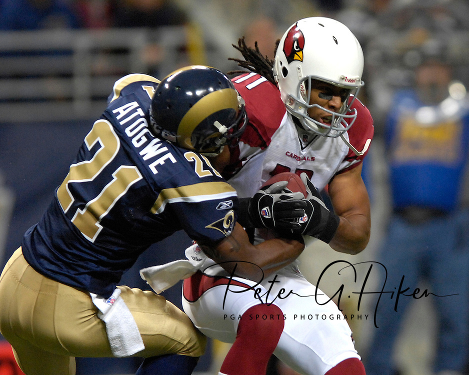 St. Louis Rams Oshiomogho Stogwe (21) wraps up Arizona wide receiver Larry Fitzgerald (11) after a catch in the first half, at the Edward Jones Dome in St. Louis, Missouri, December 3, 2006.  The Cardinals beat the Rams 34-20.<br />
