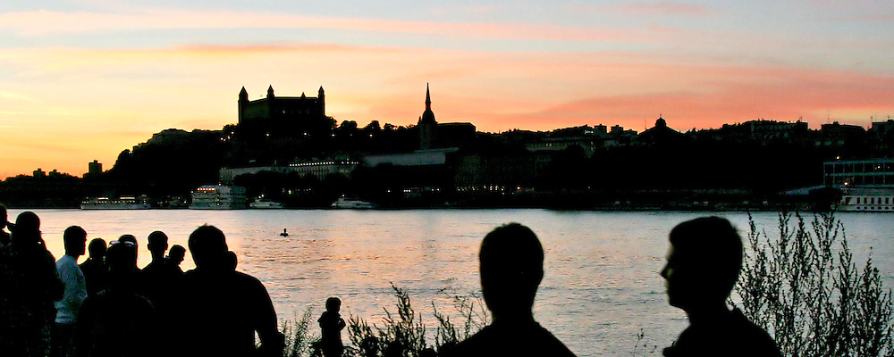 The silhouette of Bratislava castle over Danube river with silhouettes of people at front with the whole scene lit by an evening sky.