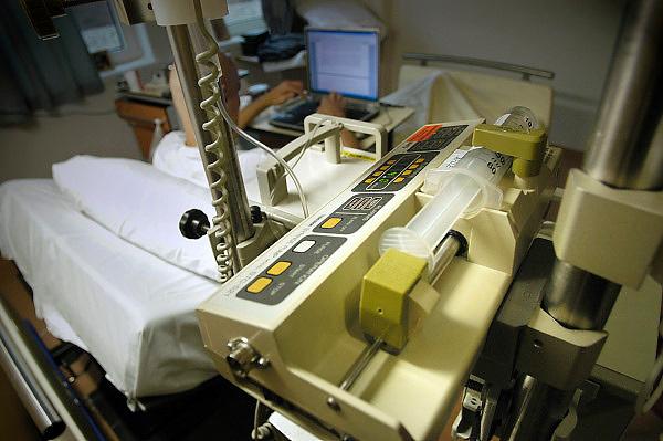 Nederland, Nijmegen, 25-2-2004..Patient in een academisch ziekenhuis krijgt via infuuspomp medicijnen toegediend terwijl hij met zijn labtop computer bezig is. Kankerbestrijding, ziekenhuisbed, kosten gezondheidszorg, landurige ziekte, pijnbestrijding, geneesmiddelen. UMCN Radboud...Foto: flip Franssen