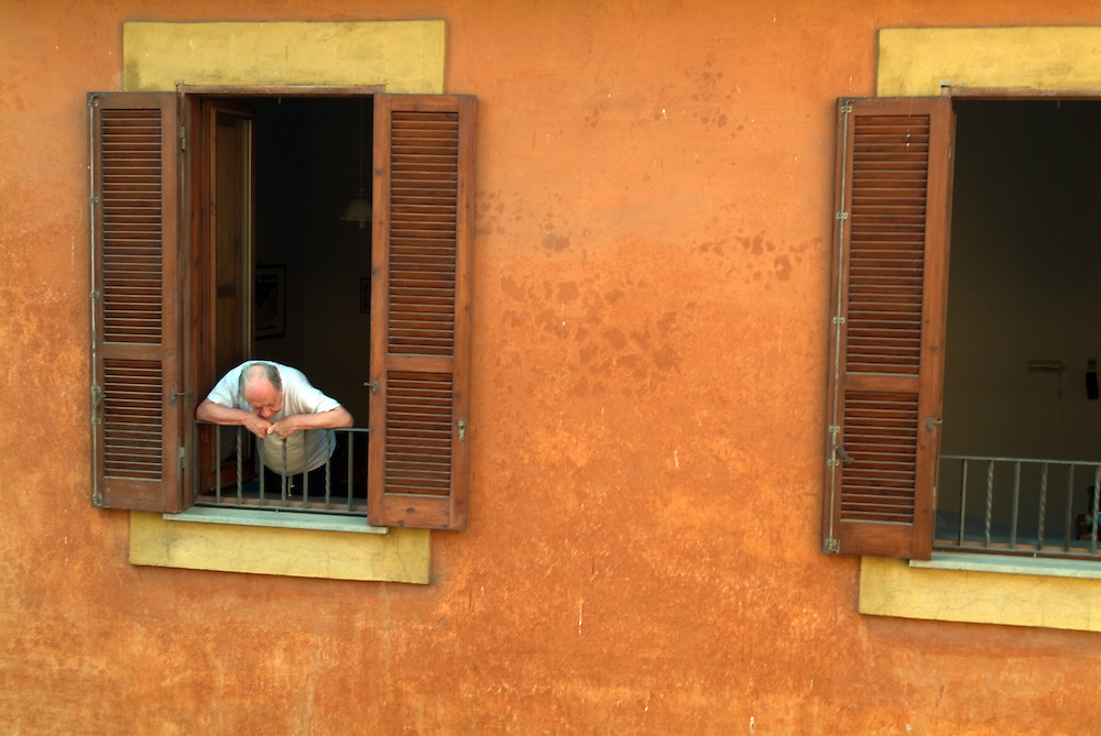 Old man looks from his window down to the street below in Rome, Italy