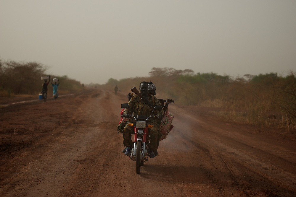 April 24, 2012 - Panakuach, South Sudan: SPLA soldiers riding a motorbike in direction to the frontline in near Panakuach village, 70 kilometers north of Bentiu. In the background a group of IDPs flee the combats...South Sudan and their northern neighbors, Sudan, have in the past two weeks been involved in heavily clashes over border disputes. Bentiu and neighboring villages have been under constant bombardment by the troops os Karthoum , who established their positions around 10 kilometers into South Sudan's territory. The international community is concerned about the possibility of a full on war between the two countries. (Paulo Nunes dos Santos/Polaris)